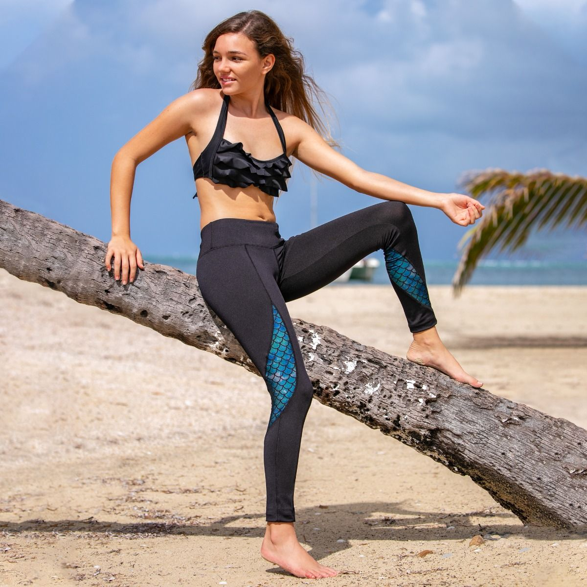 3d700229374273 ... a girl sits on a palm tree and shows of her black mermaid scale leggings