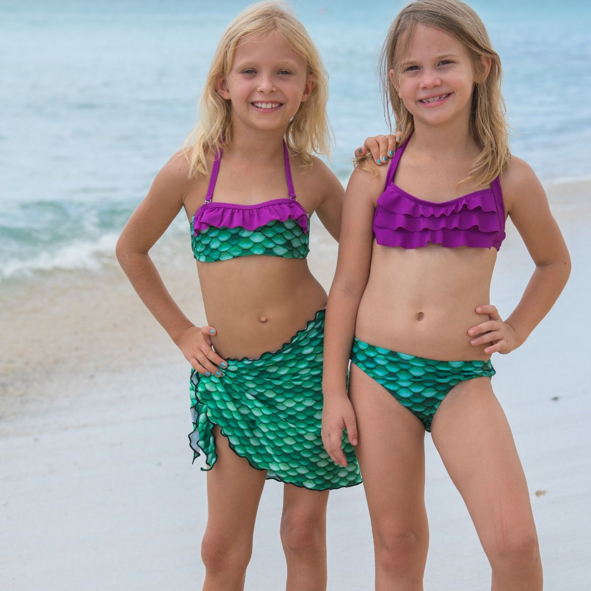9acf39f6ff665f celtic green mermaid scale sarong 2 girls wearing celtic green swimwear are  standing on a sandy beach. ...