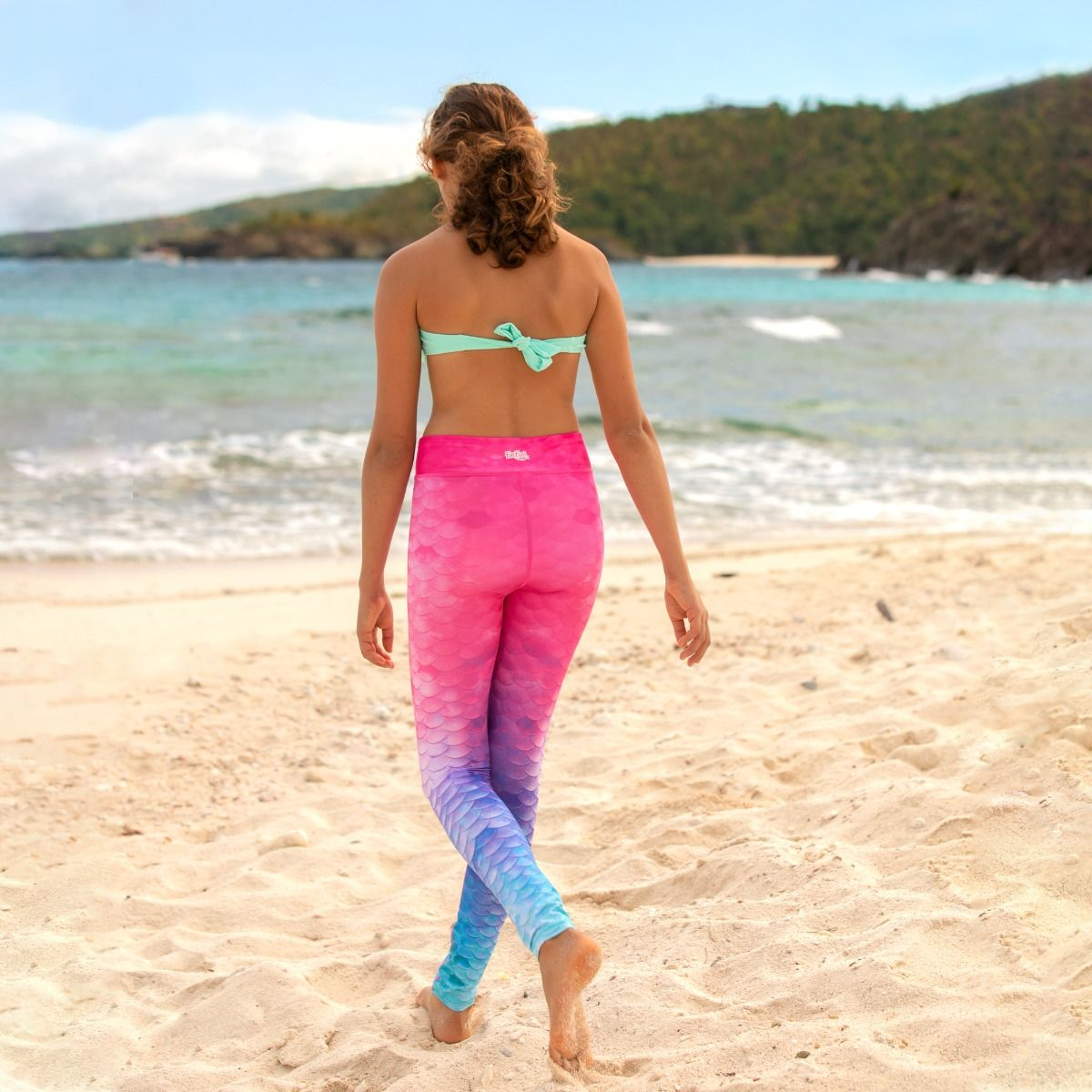 b98b52bde55 ... a young girl walks on the beach looking at the sand while wearing pink  to blue a kid wears pink to blue ombre mermaid scale leggings ...
