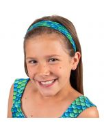 A young girl is smiling as she wears a blue and green mermaid scale headband