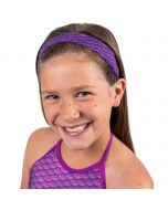 a young girl is happy as she wears a purple mermaid scale headband that matches her tankini top