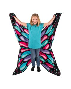 A smiling girl wearing A brightly colored butterfly blanket