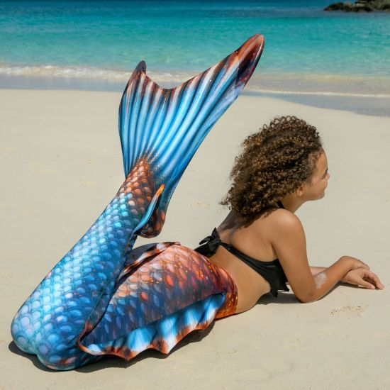 a young girl looks like a mermaid with her blue and bronze mermaid tail as she lays on the sandy beach