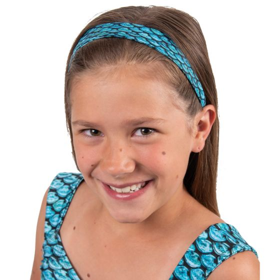 A young girl is smiling as she wears a Tidal Teal mermaid scale headband