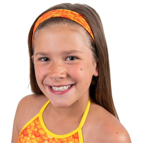 A young girl is smiling as she wears a orange and yellow mermaid scale headband